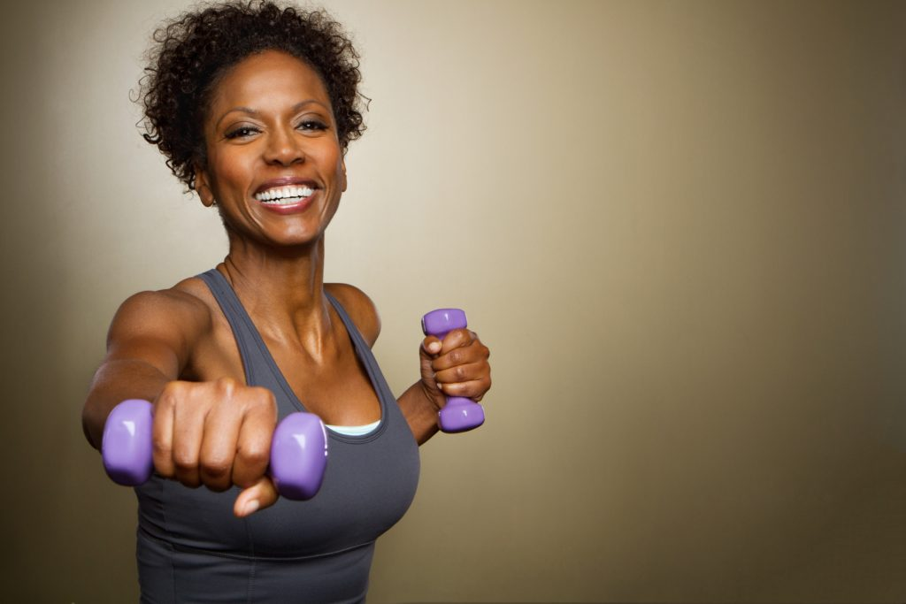 African American fit woman lifting weights smiling.
